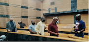 Five of the six accused make their way out of court following the postponement of the Marikana trial at the North West High Court on Friday.