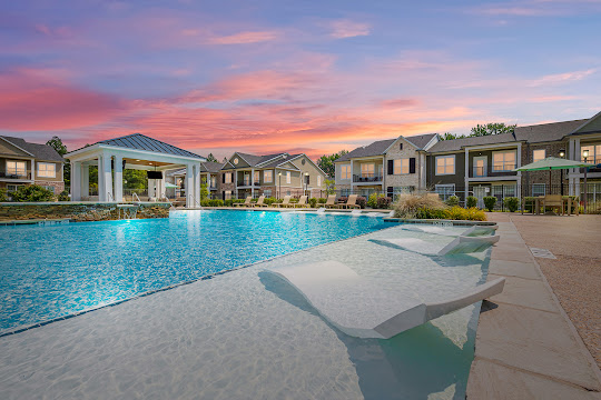 Resort-style swimming pool and hot tub with lounge chairs next to apartment buildings at dusk
