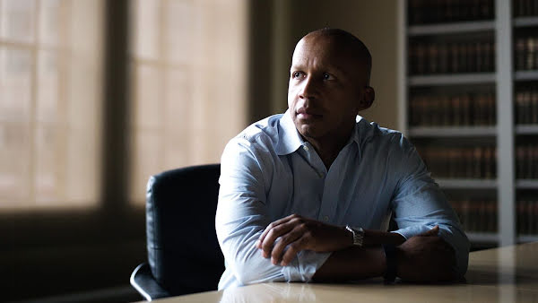 Bryan Stevenson, founder and Executive Director of the Equal Justice Initiative, sitting at a desk