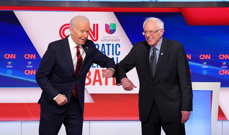 Democratic US presidential candidates former vice president Joe Biden and senator Bernie Sanders do an elbow bump instead of a handshake as they greet other before the start of the 11th Democratic candidates debate of the 2020 US presidential campaign, held in CNN's Washington studios without an audience because of the global coronavirus pandemic, in Washington, US, on March 15 2020.