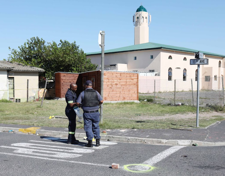 Police officers investigate the crime scene in Hazendal, near Athlone, where one person was killed outside the mosque on March 15 2019.