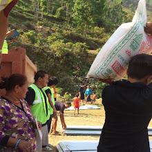 Photo: Nuestros voluntarios reparten sacos de arroz y láminas de metal a las familias afectadas por el terremoto.