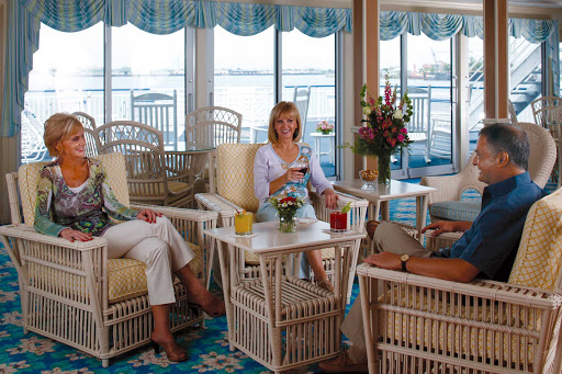 Queen-of-the-Mississippi-Sky-Lounge.jpg - Sit comfortably on white wicker chairs, chat with your friends and enjoy the views from the floor-to-ceiling windows in the Sky Lounge of your American Cruise Lines ship.