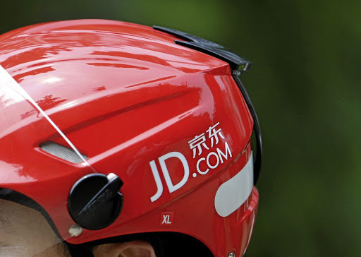 A JD.com logo is seen on the helmet of a delivery man in Beijing. Picture:REUTERS