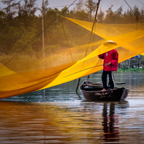 © Chantal Reed Local fisherman inspecting his nets for his morning catch, in Hoi An, Vietnam by . Reedd2 - People Street & Candids ( water, fishermen, dawn, boats, vietnam, thu bon river, hội an, fishing, nets, river. )