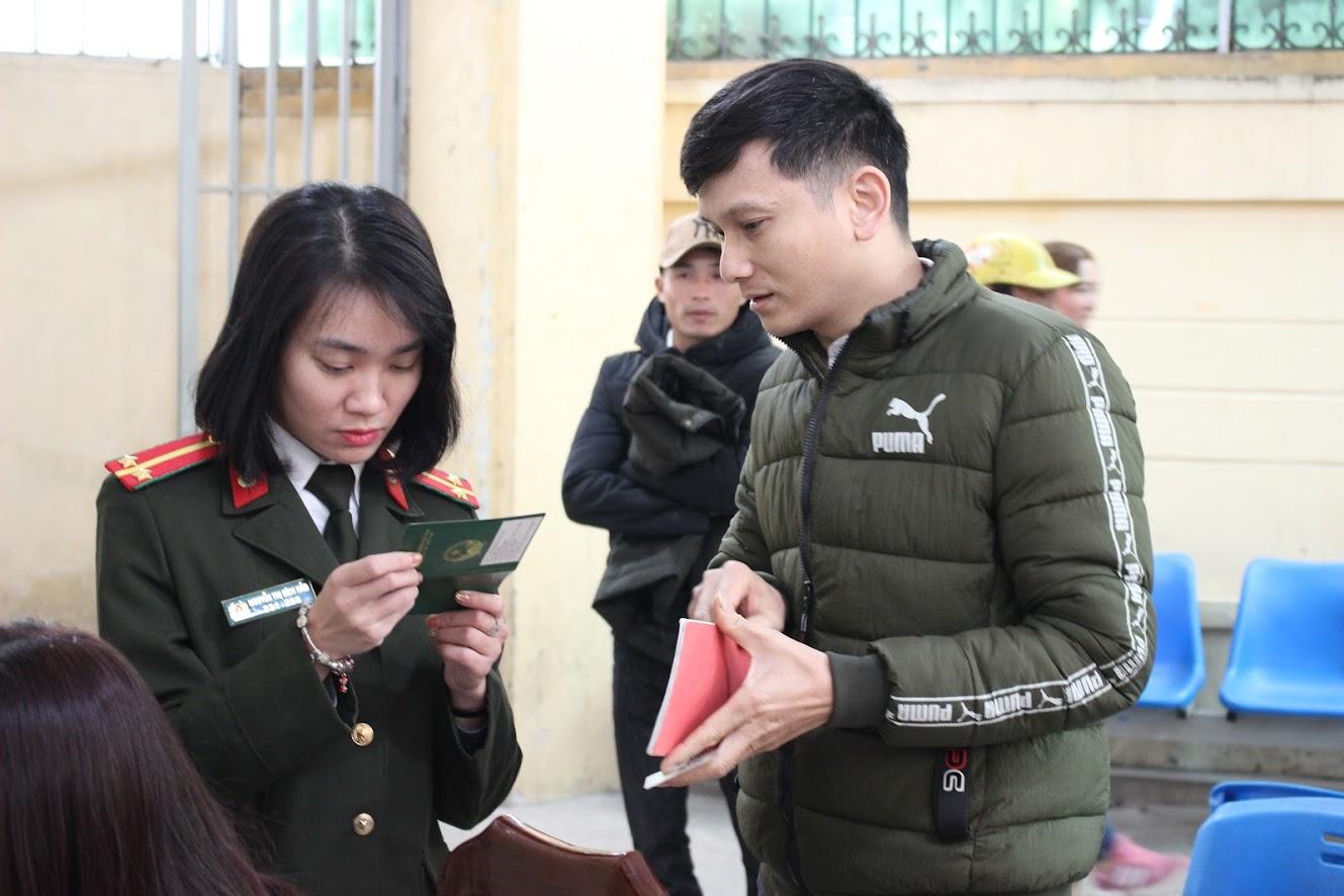 Nữ trung úy kiểm tra lại thông tin để hướng dẫn người dân làm thủ tục gia hạn hộ chiếu