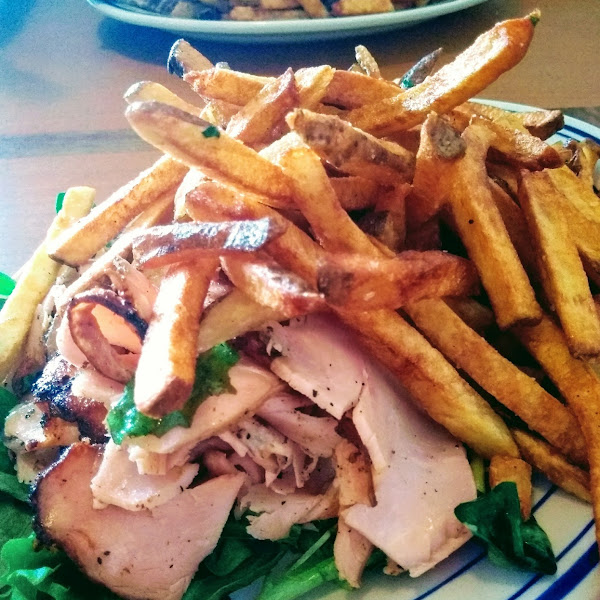 Turkey pastrami on greens with house cut fries.