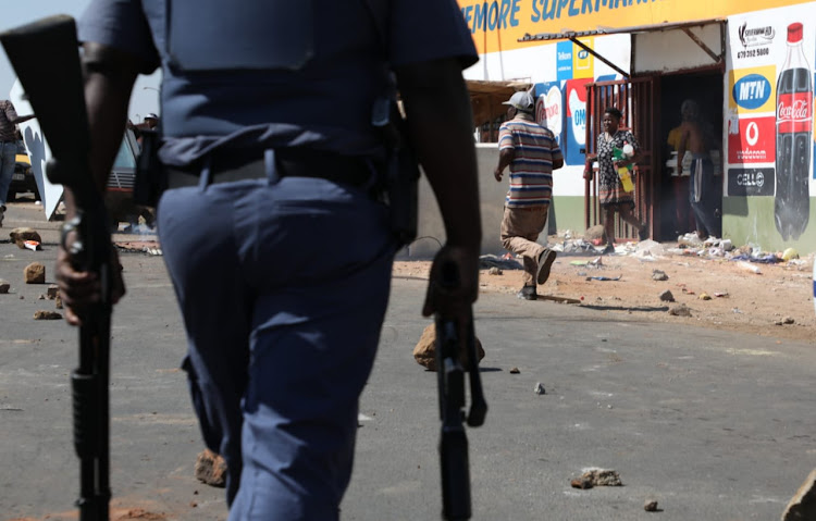 Residents of Jabavu, Soweto, loot a foreign-owned spaza shop after Banele Qhayiso was allegedly shot dead by a shop owner on August 29, 2018.