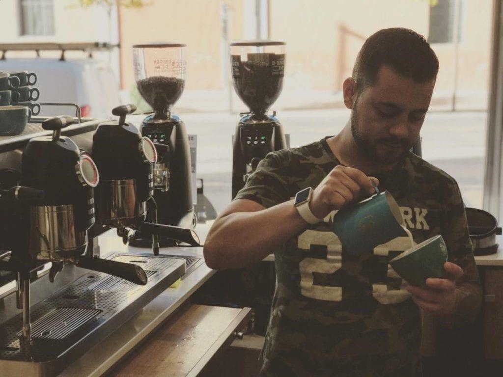 Javier Carrión vierte un cappuccino para un cliente