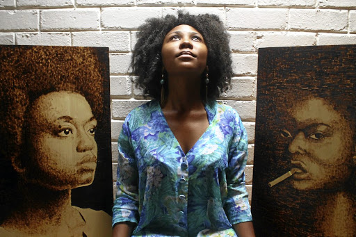 Phenyo Mel Madiba, between  two of her portraits.