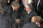 The spirit of Nelson Mandela inspires US President Barack Obama to shake hands with Cuban President Raul Castro Ruz at FNB Stadium yesterday.