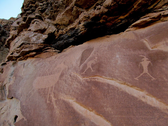 Archer (barely visible in upper-left) shooting a bighorn, and other human figures