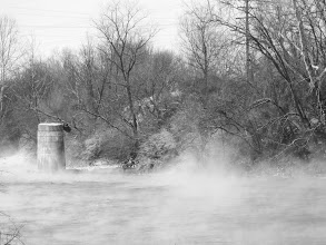 Photo: Black and white photo of mist rising from a river around the ruins of a bridge at Eastwood Park in Dayton, Ohio.