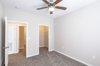 Bedroom with light gray walls, carpet, and ceiling fan