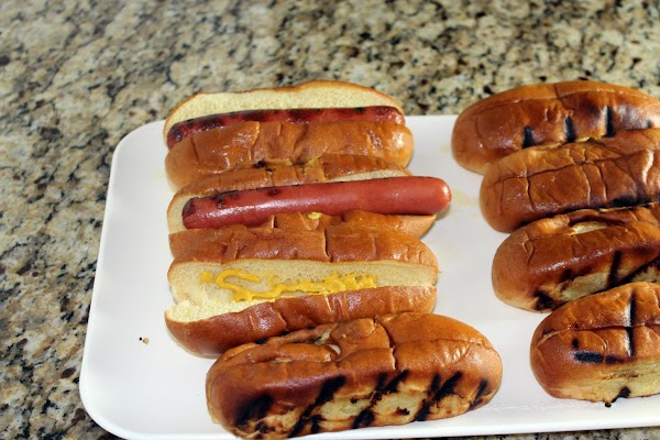 Place a little mustard along the inside of each bun and put the hot...
