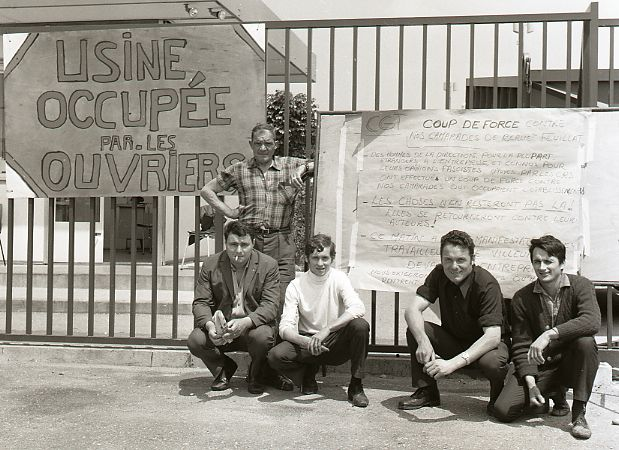 A group of workers proudly posing in front of their occupied factory.