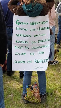 Rückenplakat: «Grenzen müssen nicht zwischen den Ländern verlaufen sondern zwischen den Menschen. Nicht aus Stacheldraht sollen sie sein sondern aus Respekt! Dora Kehr».