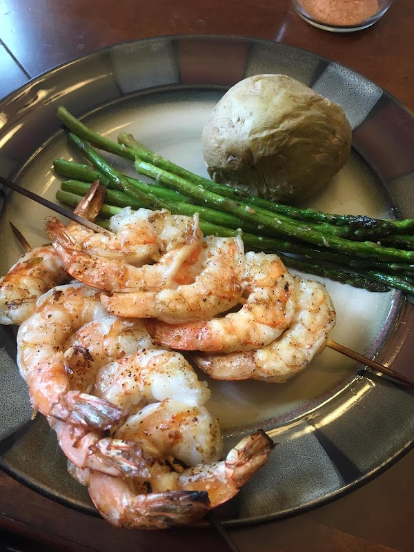 Shrimp served with asparagus sautéed in olive oil butter and garlic.
