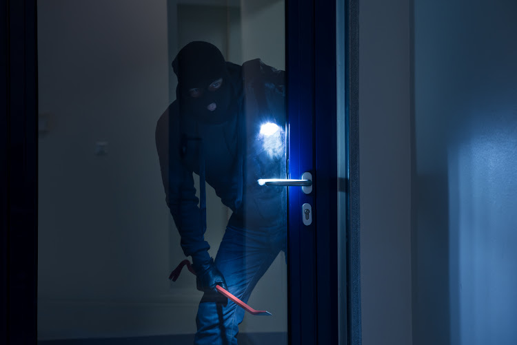 A thief with a flashlight trying to break a door.