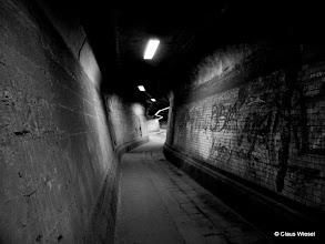 """Photo: Der Matena-Tunnel in Duisburg  Der Matena-Tunnel ist ein etwa 400 Meter langer Tunnel, der mitten unter dem aktiven Stahlwerk von Thyssen-Krupp verläuft. Er wurde im Zuge von Werkserweiterungen im Jahre 1911 auf der bestehenden Matena-Straße errichtet. Der Begriff Matena bedeutet """"Wiesenaue"""". Das Besondere an diesem Tunnel ist sein ganz eigener Charme, die Baufälligkeit und die Tatsache, dass er insbesondere im Schimanski-""""Tatort"""" häufig eine Filmkulisse war. Durch die Anpassung an die bestehende Straßenführung hat der Tunnel eine sehr eigenartige Form, die man als """"organisch"""" bezeichnen könnte. Der Tunnel ist recht kurvenreich, man kann von einem Ende nicht zum anderen sehen."""