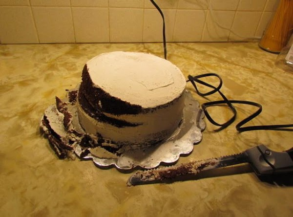 After baking your three layer cake, frost the middle sections and lightly frost the...