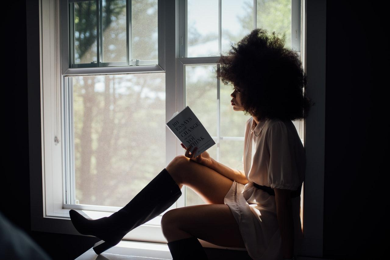 A woman reading a book by a windowsill