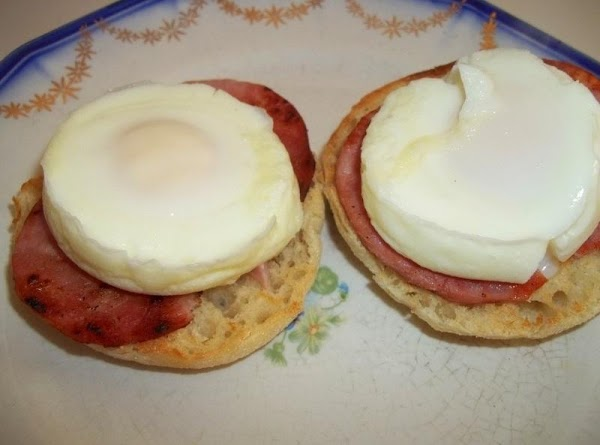 Toast muffins.  Place 2 toasted muffins halves on each plate. a slice of ham to...
