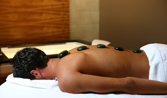 a man lying down with stones on his back during a hot stone massage