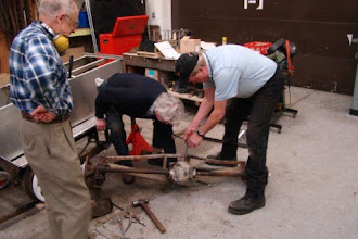 """Photo: Allan, Ross and Steve working on the rear axle disassembly.  Note the bend/sag in the 1""""x1"""" horizontal aluminum frame pieces.  Could we have possibly bent these with our fork-lift exercises?"""