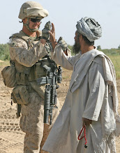 Photo: Sgt. Cody T. Romriell, a combat engineer with 2nd Battalion, 9th Marines, high-fives a local after helping him unclog a backed-up canal during the construction of Typhoon 3 in Marja, Afghanistan, Sep, 9. Marine engineers with 2/9 have been constructing new patrol bases in their area of operation in order to increase force protection. Typhoon 3 is one of the many being built.