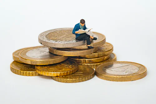 A person sitting on a pile of coins  Description automatically generated with medium confidence