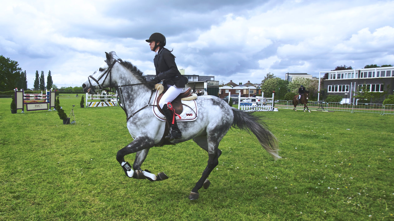 child horse riding on a  grey pony at canter in a jumping ring
