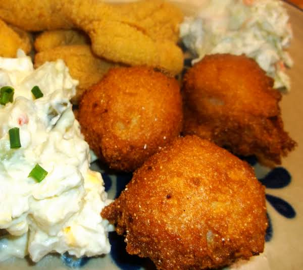 3 Hush Puppies On Plate With Potato Salad, Fried Fish And Coleslaw.
