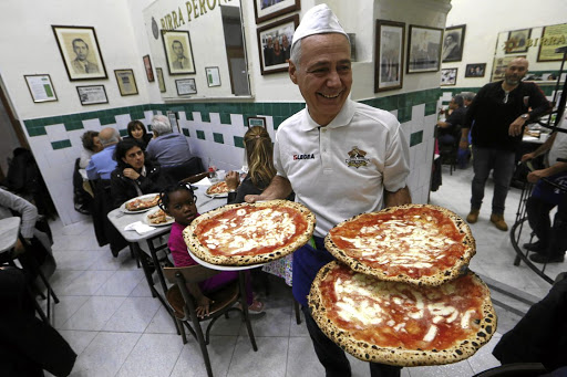 A waiter serves pizza Margherita at L'Antica Pizzeria da Michele in Naples, Italy. Picture: REUTERS