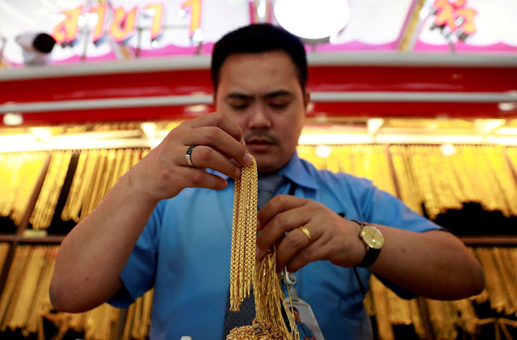 A man holds necklaces in a gold shop in Chinatown in Bangkok, Thailand. Picture: REUTERS/SOE ZEYA TUN
