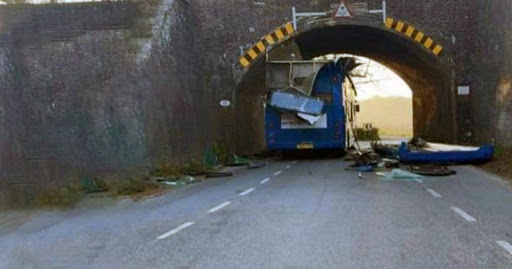 Driver and passenger injured after bus smashes into bridge, tearing off roof