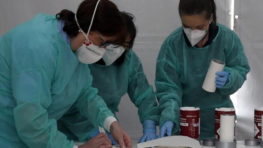 Tres enfermeras trabajan protegidas con mascarillas.