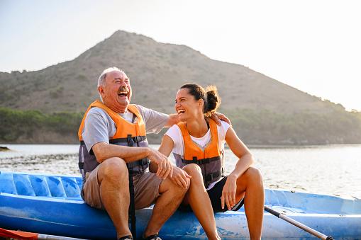 Pai e filha sentados em uma canoa, no mar, abraçados e rindo.