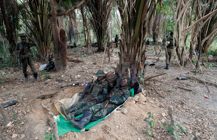 Congolese soldiers from the Armed Forces of the Democratic Republic of Congo rest in an ADF rebel camp, near the town of Kimbau, North Kivu Province, Democratic Republic of Congo.