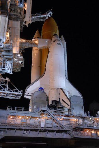 Rollback on Launch Pad 39A, Space Shuttle Atlantis stands bathed in lights atop a mobile launch platform.
