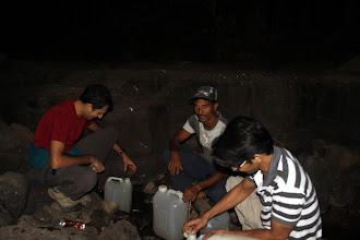 Photo: Filling 25L of water before heading up. Yes, that is a cup made from a plastic bottle we found on the ground. Yes, that is garbage beside our water source. No, we did not filter the water before drinking it! Sunny Jamshedji, Guru and Ajit Bobhate. (Courtesy Richie Kher)