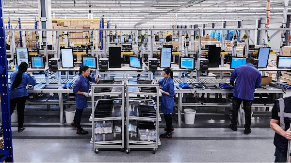 People working in a computer manufacturing facility, assembling computer parts.