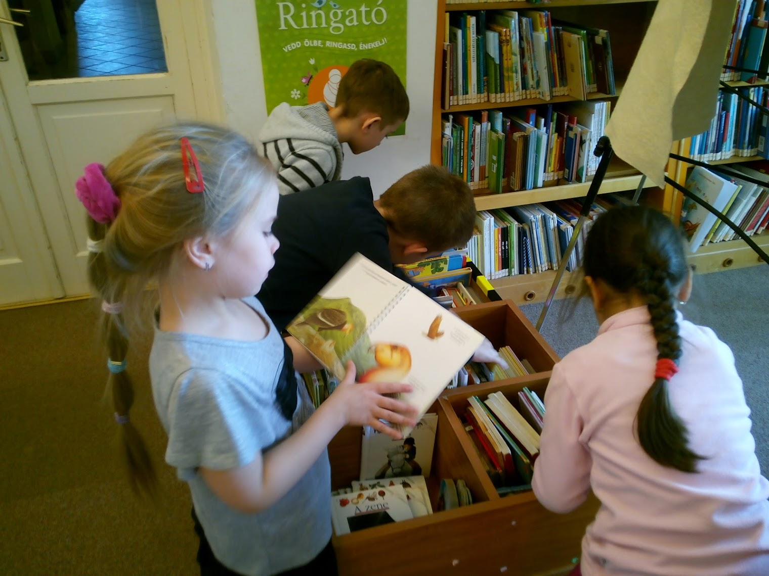 Könyvet böngésző gyerekek