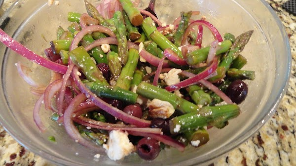 Mixing asparagus with onion, olives, Feta cheese, and oil.