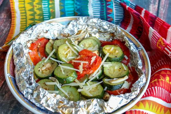 Zucchini And Tomato Foil Packets On A Plate.