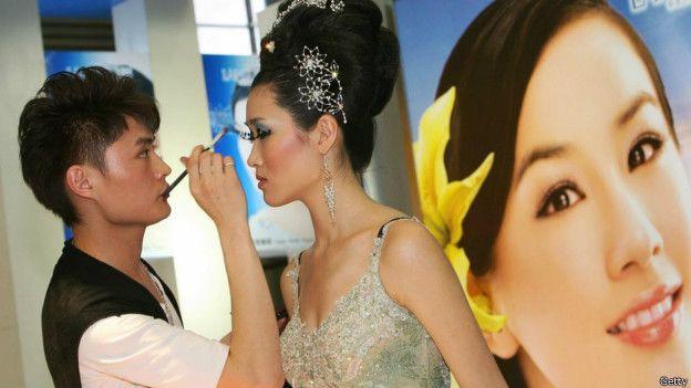 Una modelo china siendo maquillada