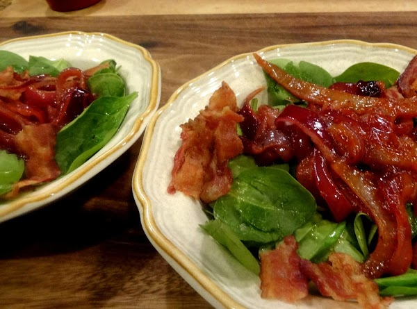 Add the hot bacon and onion dressing to the bowl of prepared raw spinach....