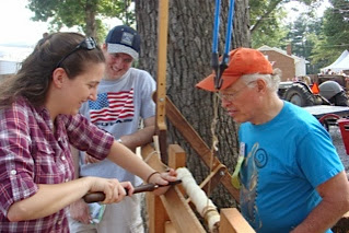 Photo: Phil Brown coaching a fair-goer in the fine points of pole lathe turning