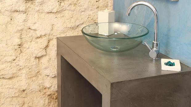 Mairage du béton ciré avec les pierres apparentes d'un mur de salle de bain
