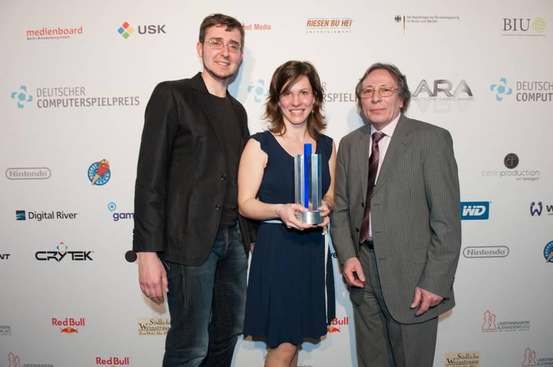 Photo: Sonderpreis Browsergame TRAUMA: Krystian Majewski, Veronika Barth, Jurymitglied Jürgen Hilse v.l.n.r. © Deutscher Computerspielpreis 2012 / Ulf Büschleb